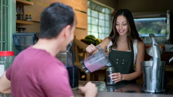A female barista pouring a smoothie for a male customer
