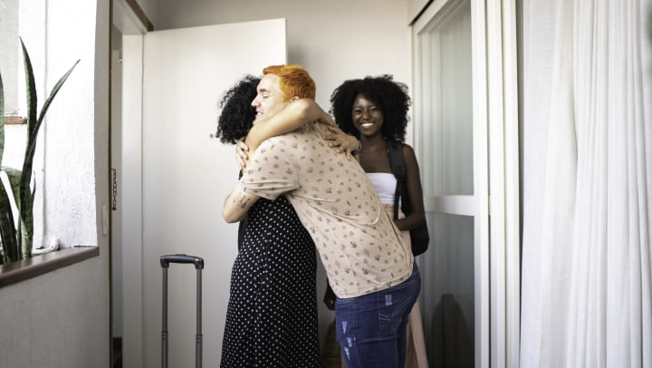 A friend acting as a host welcomes guests into home with hugs.