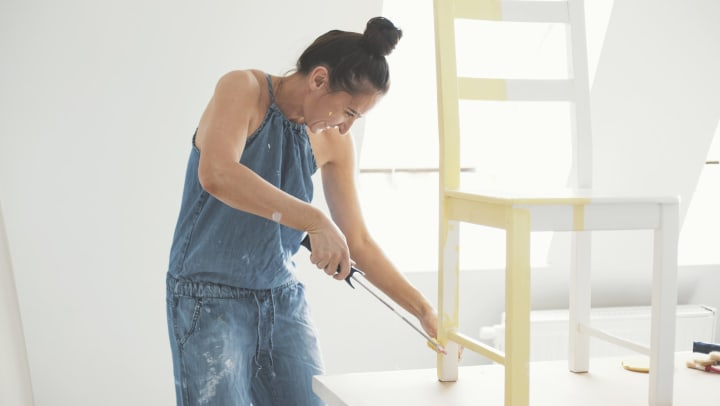 Resident painting a chair in her new home at The Enclave in Brunswick, Georgia