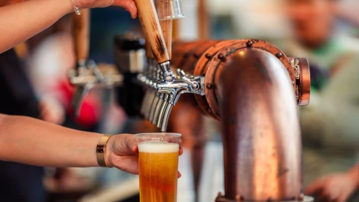 Bartender pulling a fresh beer on tap at a brewpub near Olympus Boulevard in Frisco, Texas