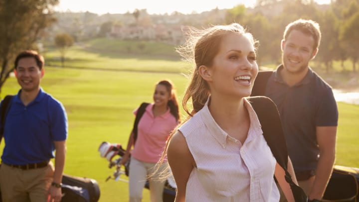 Group of young golfers smiling and walking toward the camera in San Diego, California near Olympus Corsair