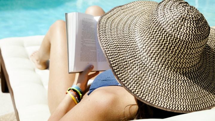 Woman enjoying a book by the pool at Olympus Steelyard in Chandler, Arizona