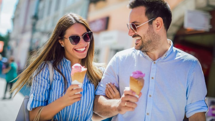 Couple on a walk in the sun enjoying ice cream in Albuquerque, New Mexico near Olympus Solaire