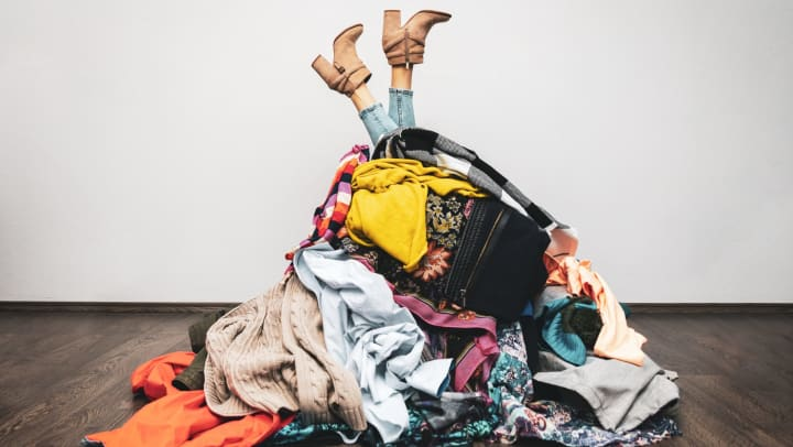 A woman's legs stick out from the top of a huge pile of clothes.