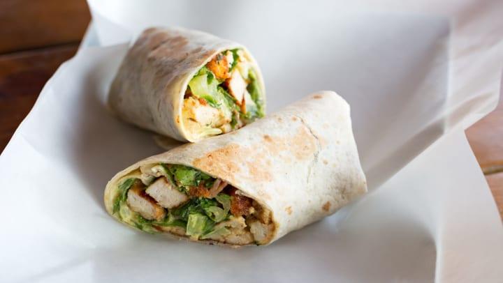 Chicken Caesar salad sandwich wrap on a white parchment paper.