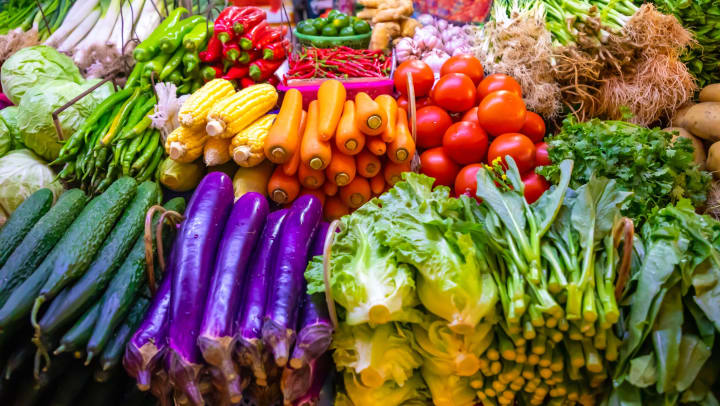 A produce stand with a selection of colorful vegetables including carrots, lettuce, tomatoes, green onions, and peppers