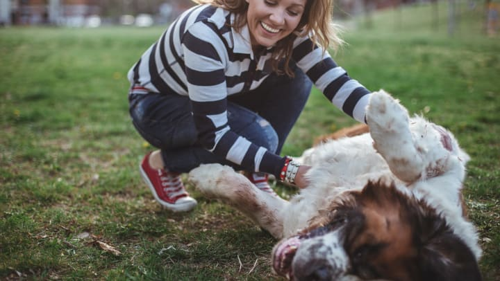 Woman petting a dog's belly and smiling while outdoors.