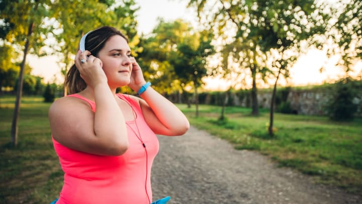 A young woman preparing her music for a run along a nature trail.