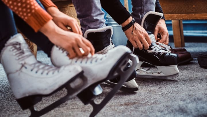 A close up of a woman's hands lacing up figure skates and a man's hands lacing up hockey skates.