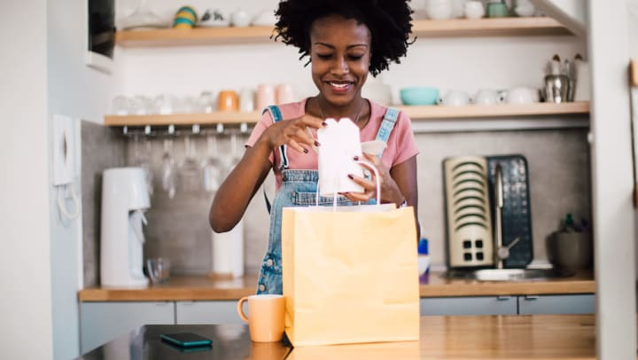 Woman pulling a takeout container out of a paper bag and smiling.