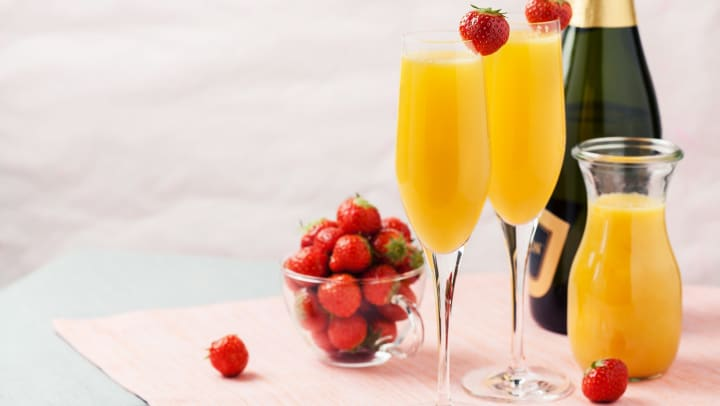 Mimosa cocktails and strawberries.