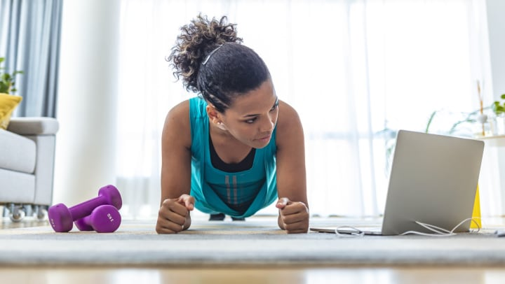 Low viewpoint of young woman in plank pose with dumbbells and laptop on the floor in a light-filled living room