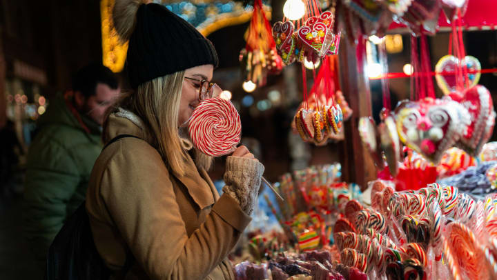 A woman standing in front of a display of candy holding a large sucker.