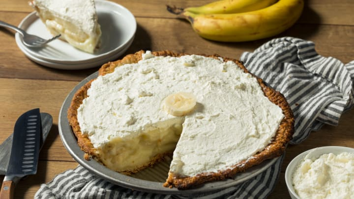 A homemade banana cream pie sits on a table, with one slice sitting on a plate behind it.