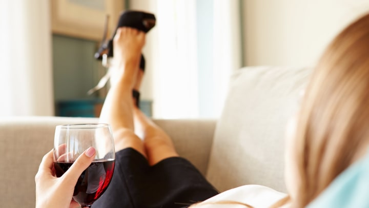 Woman lounging on a couch kicking her feet up, with a glass of red wine.