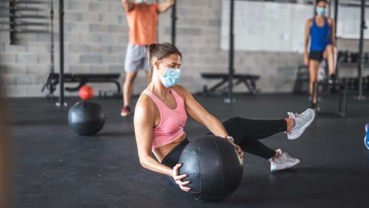 A woman seated on the ground of a gym holding a medicine ball on one side of her body, with a man and a woman exercising in the background