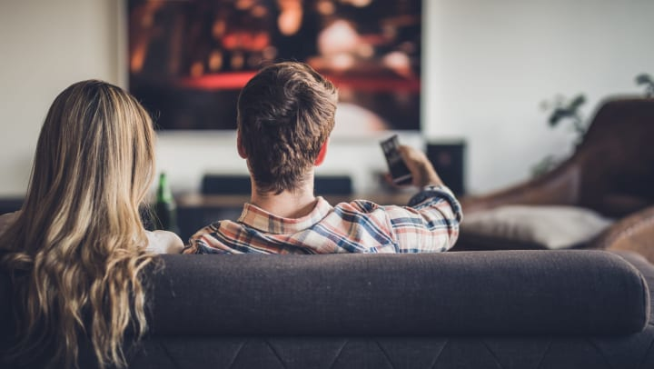 A man and a woman sitting on a couch, facing away from us, watching TV.
