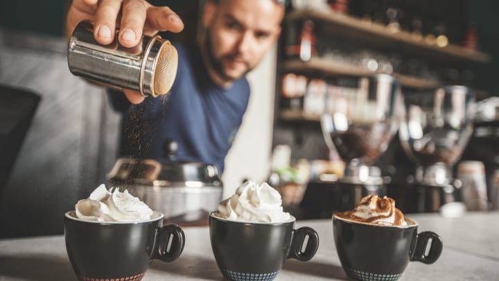 View inside a coffee shop with three cups of coffee sitting on the bar and a barista shaking cinnamon over the coffee