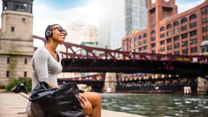 Young woman with headphones on listening to music in Chicago
