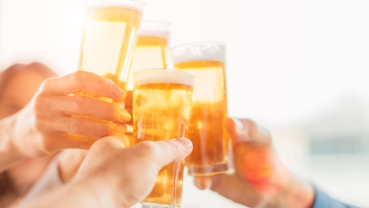 Close-up of four hands holding glasses full of beer and clanging them against one another