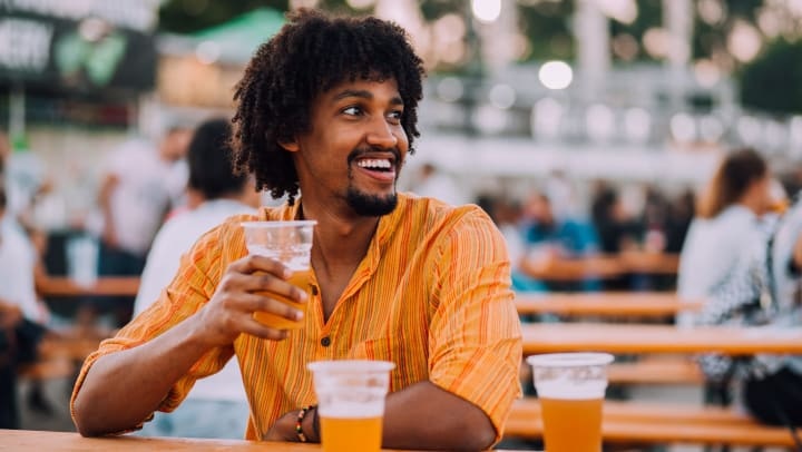 A smiling man sitting at a table on an outdoor patio while enjoying a beer.