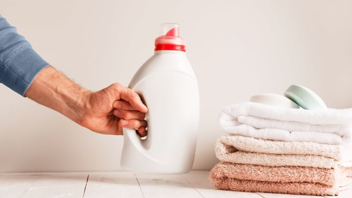 Person picking up a container of soap, which is next to a pile of towels with bars of soap on top of them