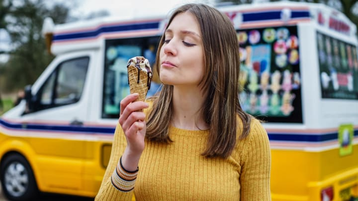 A woman standing in front of an icecream truck eating icecream in a waffle cone.
