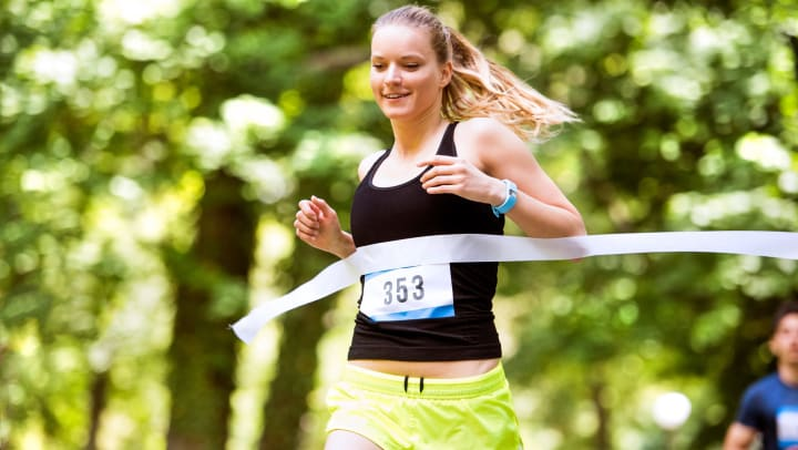 Smiling young woman running in a park and crossing a finish line banner