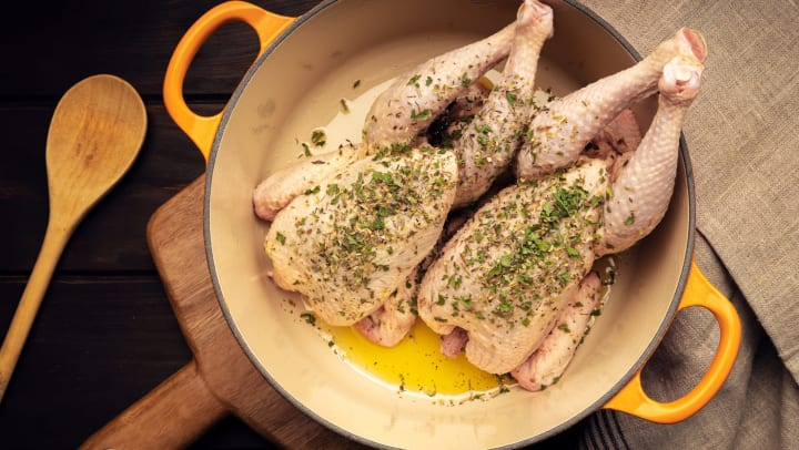 Two seasoned raw chickens in a cast iron enamel pan on a cutting board with a wooden spoon lying on the table next to it.