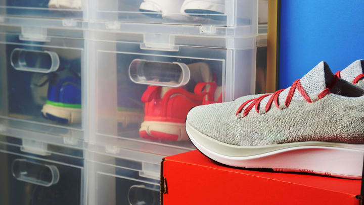 Sneakers sitting on a shoebox with clear containers full of sneaker pairs in the background.