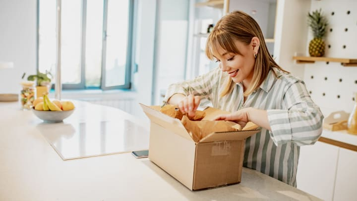Young woman unpacking the package she ordered online.