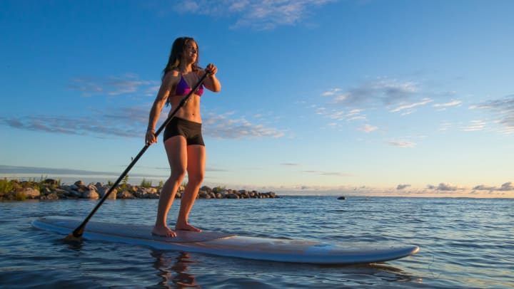 Young woman paddling on a stand up paddle board on the water at sunset