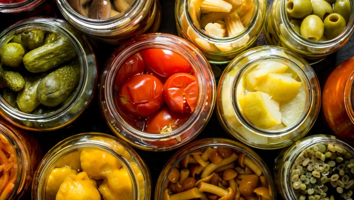 An eagle eye view of an array of pickled goods in open jars.