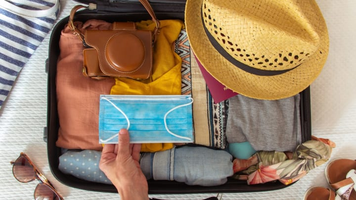 Hand putting a face mask in a suitcase. There are other accessories in the bag, including a hat, a camera, and a bikini.