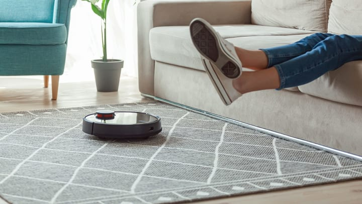 Robot vacuum cleaner cleaning carpet while a woman is sitting on the sofa raising her legs up.
