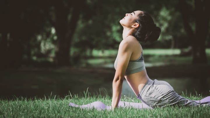 Woman doing yoga on mat in park