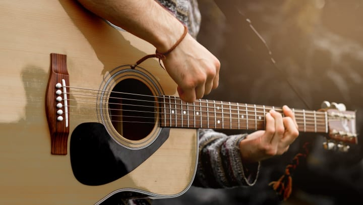 Close up of a person playing a guitar
