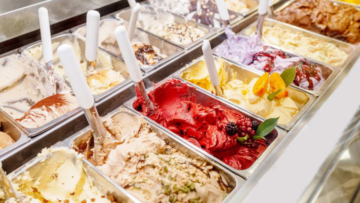 Various flavors of ice cream displayed behind glass in a dessert shop.