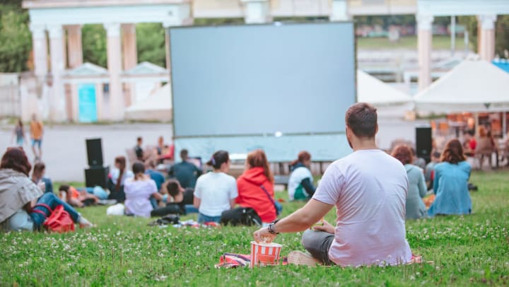 Group of people sitting on a lawn facing a large projector screen with a man in focus grabbing popcorn out of a bowl.