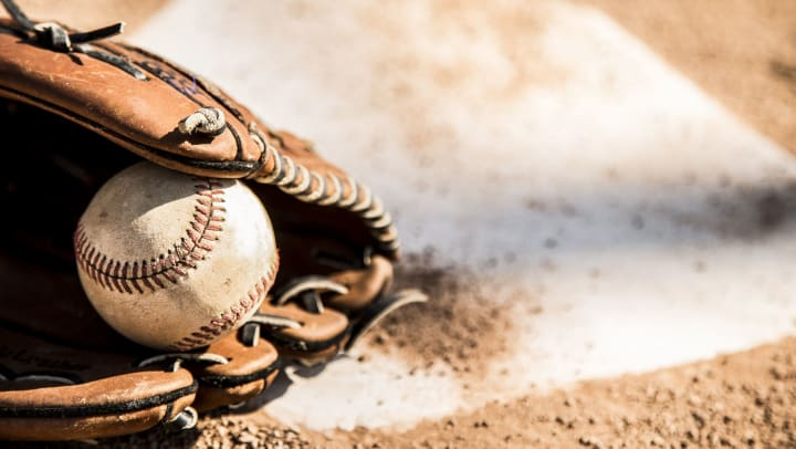 A baseball inside a baseball glove sitting atop home plate