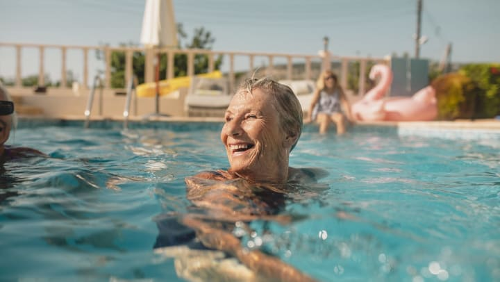 Elderly woman smiling in a pool with a person and pink flamingo behind her.