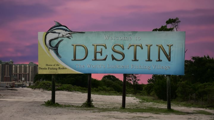 """A large sign that reads, """"Welcome to Destin, The World's Luckiest Fishing Village,"""" with a sunset in the background"""