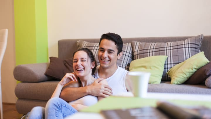Young couple watching TV and smiling while sitting on the floor and leaning against a grey couch