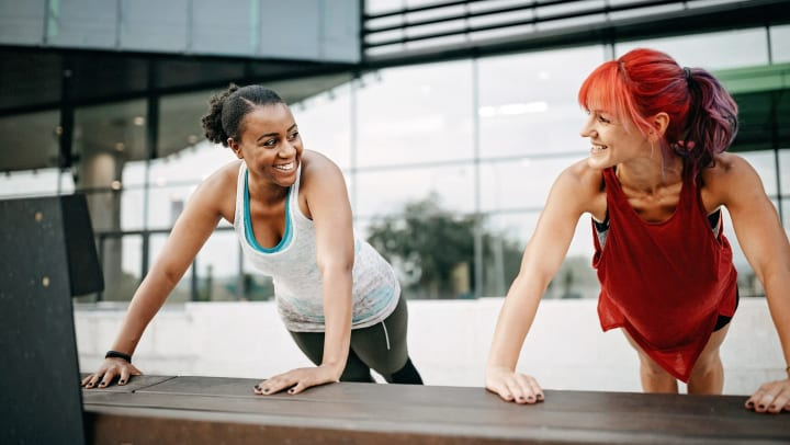 Two smiling women wearing athletic gear holding plank pose outside an office building