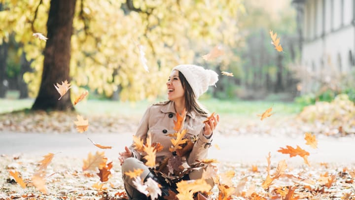 A smiling young woman is surrounded by falling leaves as she sits on the ground at a park,