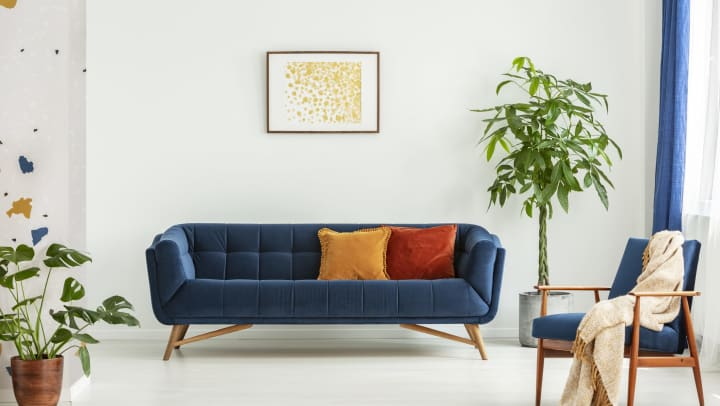 Midcentury modern chair with a blanket and a large sofa with colorful cushions in a spacious living room interior with green plants and white walls.