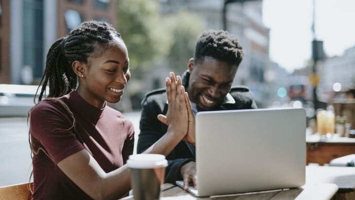 A man and a woman high five while looking at an open laptop. A to-go coffee cup sits in front of them slightly out of focus.
