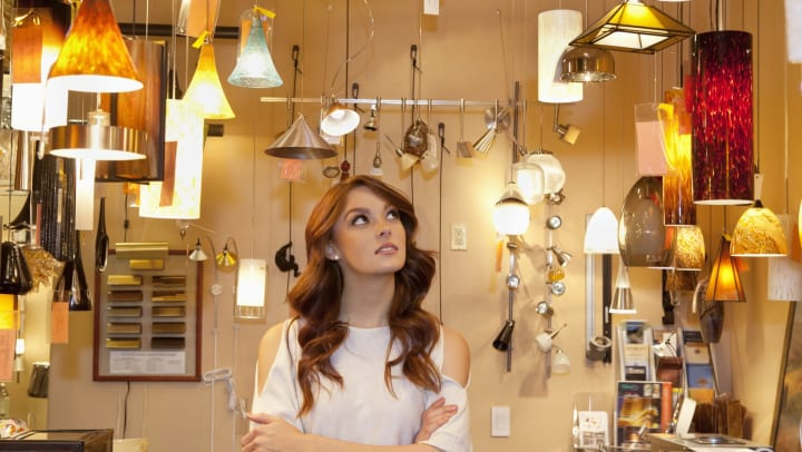 A young woman looking toward ceiling, in a shop amid various styles of hanging lamps.