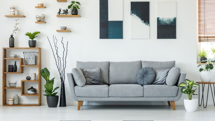 Gray couch against white wall, surrounded by modern paintings, shelving, and furniture.