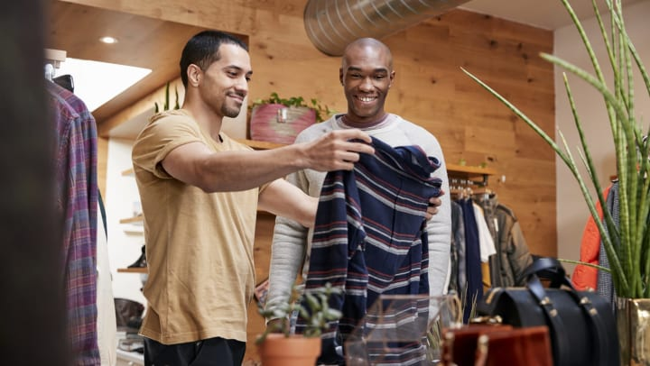 Two men in a store,  looking at a sweater and smiling.